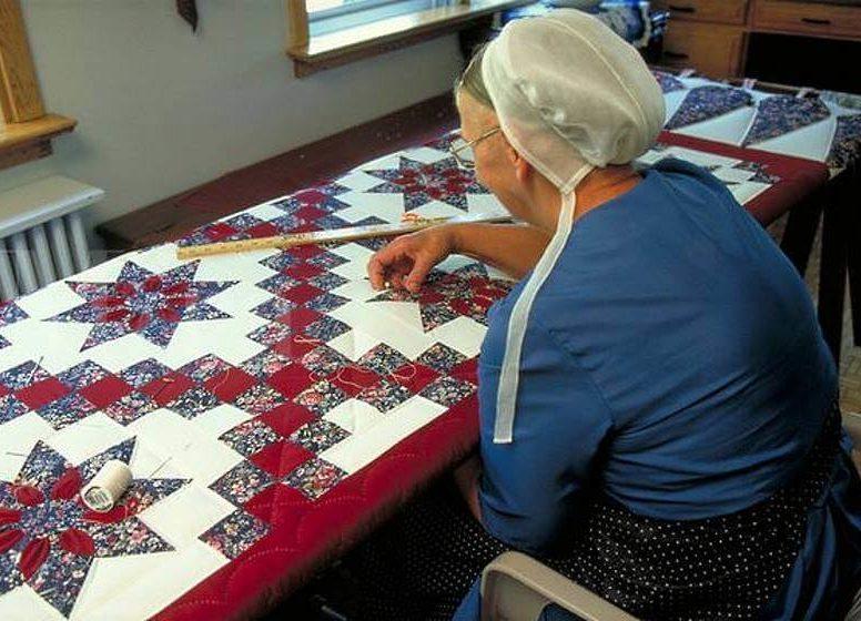 женщина амишей за лоскутным одеялом